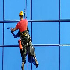 Servicio de limpieza de vidrios en altura con hombre colgado